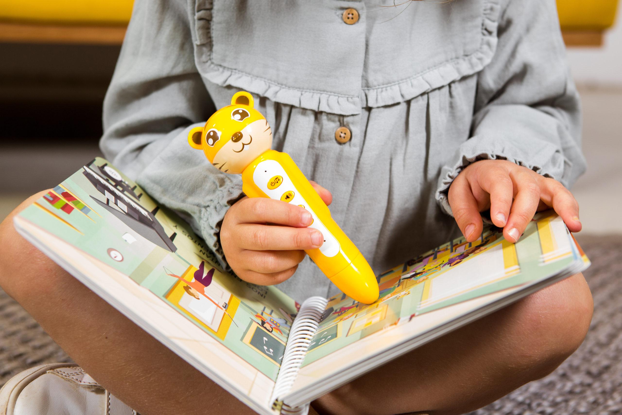 Niña usando el lápiz interactivo para leer cuento de blabook